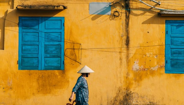 A photo by Jack Crosby of a woman walking in front of a yellow wall in Vietnam