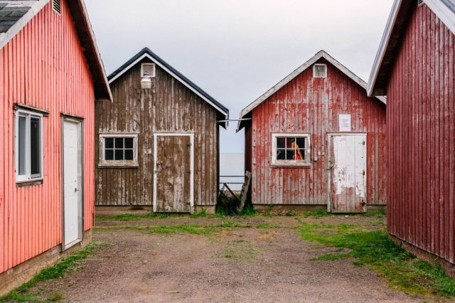 a number of brown and red wooden shacks in victoria-by-the-sea on prince edward island.