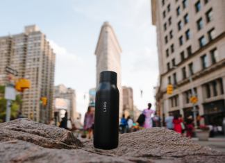 A LARQ self-clean water bottle rests on a rock with a flatiron building and cityscape in the background.