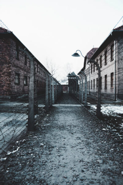 Barbed wire fences and brick buildings of Auschwitz