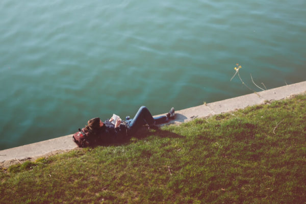 Person lays by the water reading a book