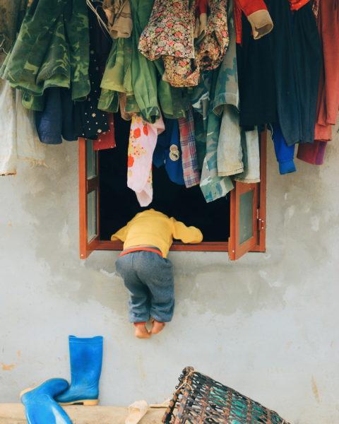 Child Climbing Through Window in Moc Chau, Vietnam