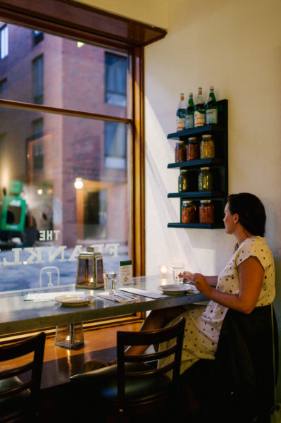 a woman sits to dine in at a window table