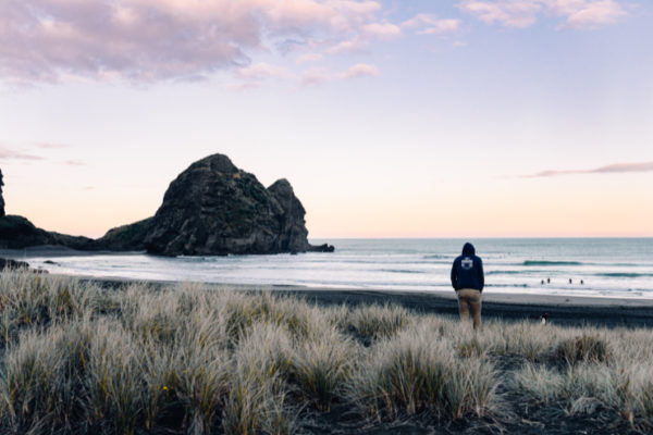 Man walks toward Lion Rock on Piha Beach, Auckland