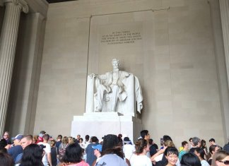 a crowd around a statue of abraham lincoln