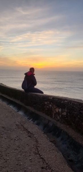 person sitting on wall by seaside