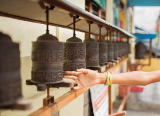 a child's hand spins a buddhist prayer wheel