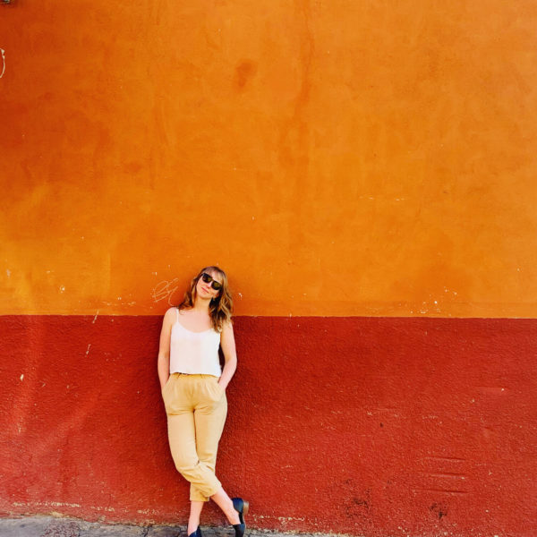 woman leaning on orange and red wall