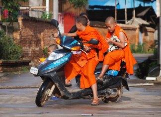 boys in orange buddhist robes riding scooter bike