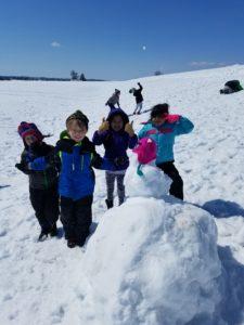 Students building a large snowman