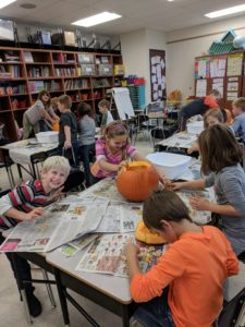 Students counting pumpkin seeds.