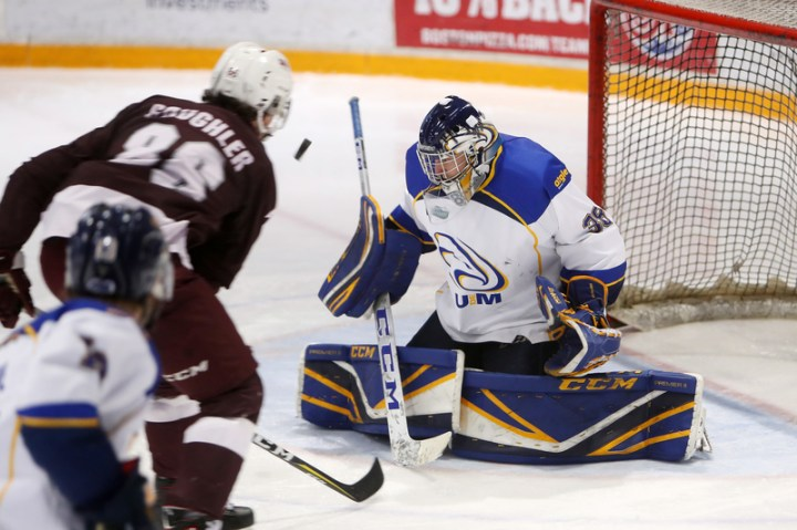 Université de Moncton Aigles Bleus goaltender Étienne Montpetit makes a save on Saint Mary's Huskies forward Jake Coughler during the AUS men's hockey conference last season.