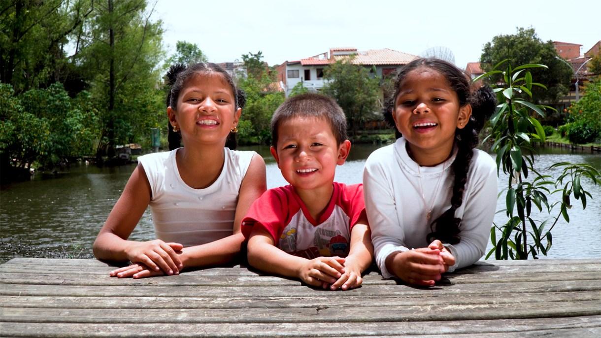 2 niñas y un niños sonríen, al fondo un río