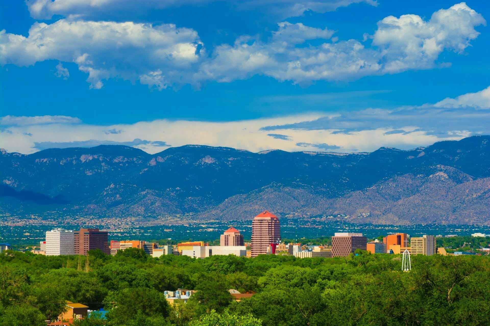 RealWealth market image featuring Albuquerque skyline, mountains, and clouds