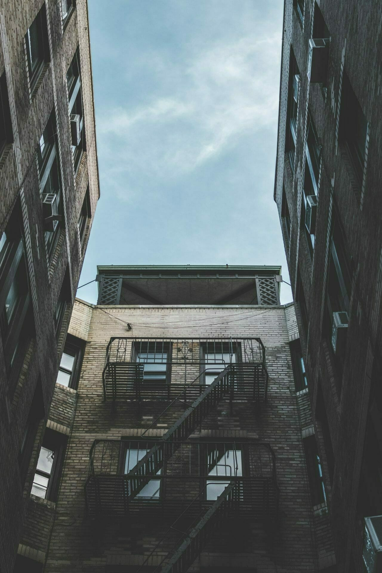 Picture of apartment building with fire escape for Real Estate News for Investors Podcast Episode #611