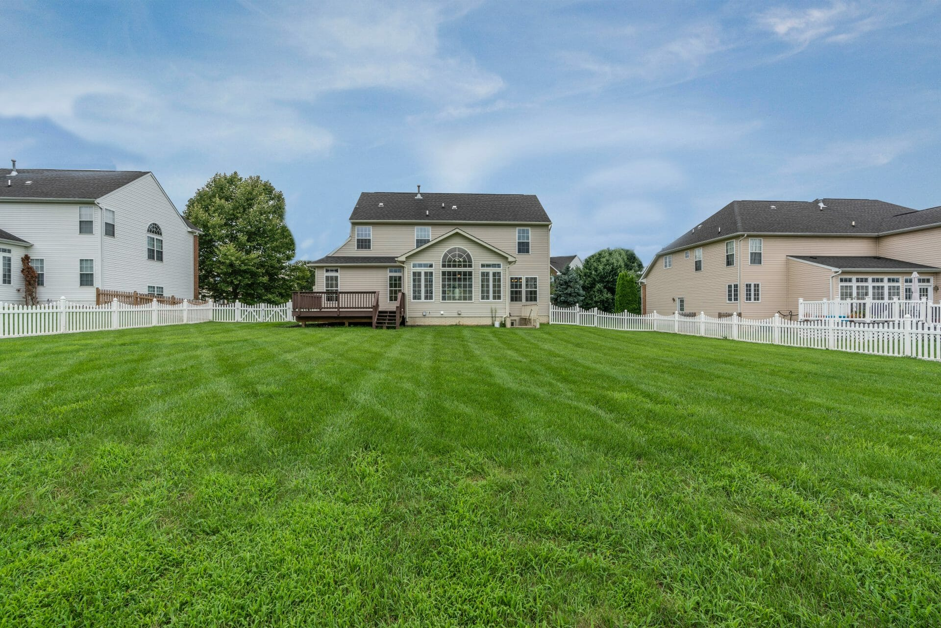 Image of yard with house and white fence for Real Estate News for Investors Podcast Episode #731