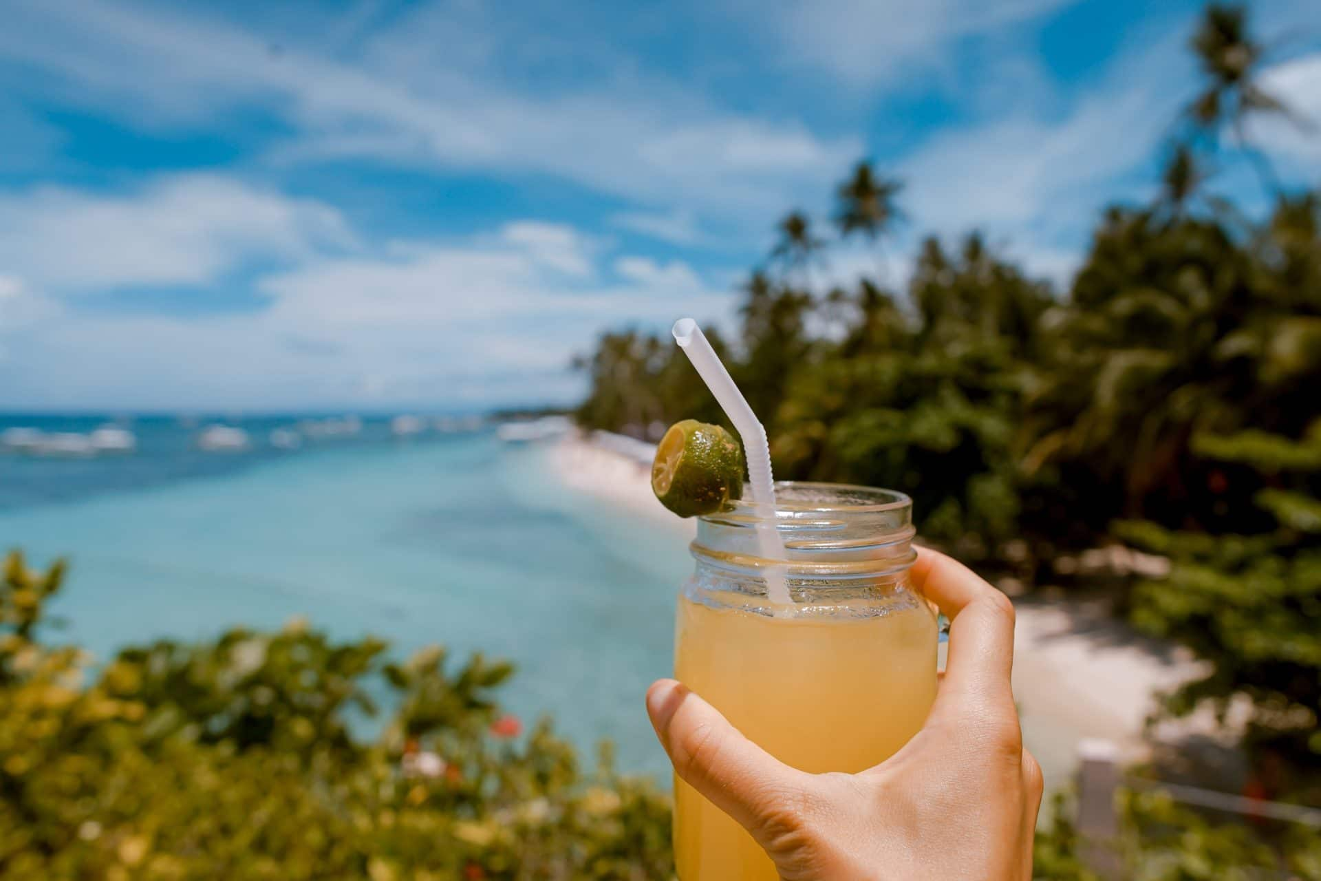 Picture of a Person holding a Drink on a Beach for Real Wealth Show Podcast Episode #644