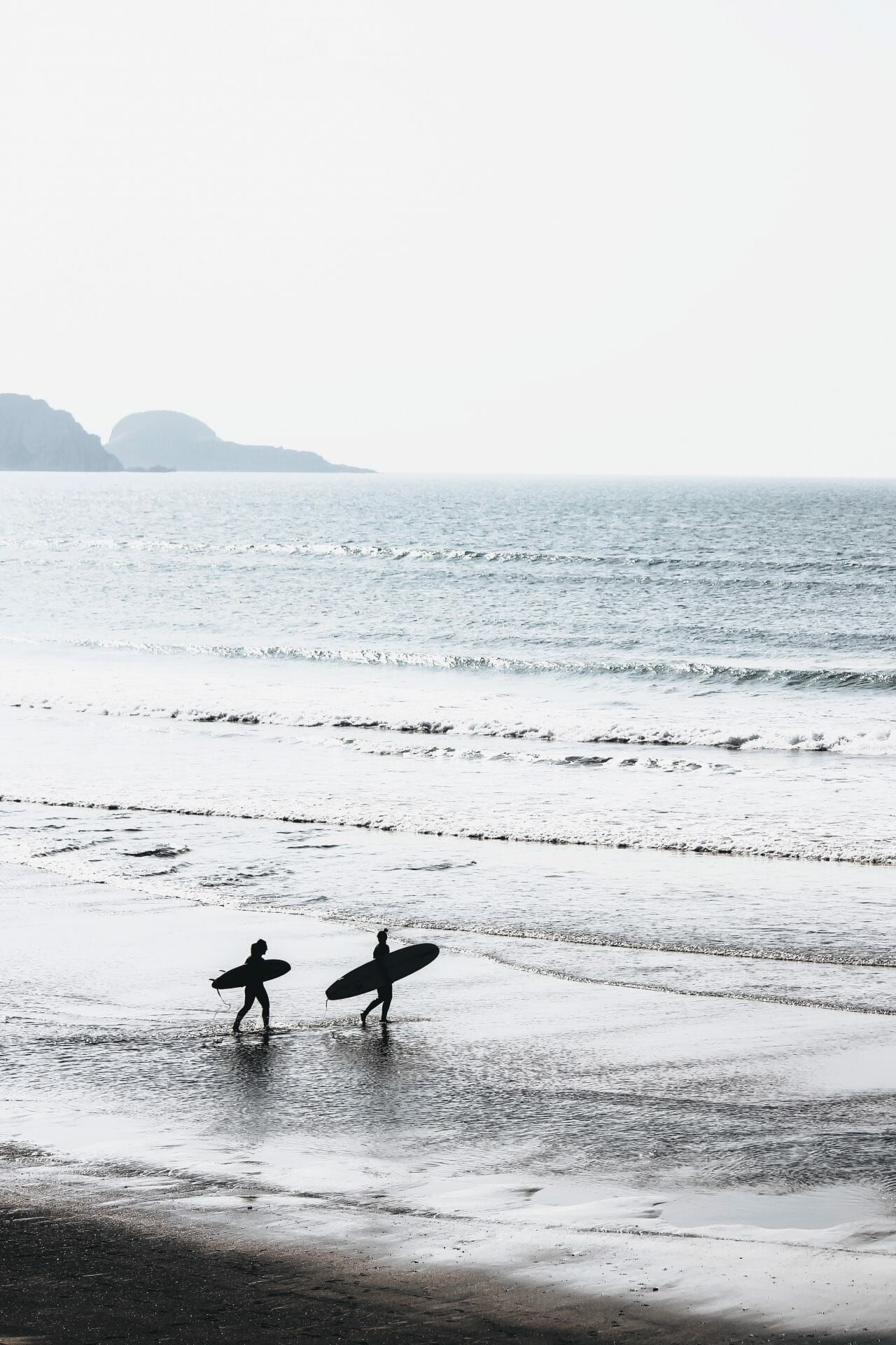 Picture of two people on beach with surfboards for Real Wealth Show Podcast Episode #690