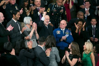 """""""Recently released from prison in Cuba, Alan Gross pumps his fist in the air from First Lady Michelle Obama's box after President Obama acknowledged him at the State of the Union address at the U.S. Capitol."""" (Official White House Photo By Chuck Kennedy)"""