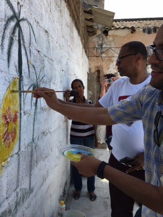 Javier Martinez, right, paints zia symbol in Havana.
