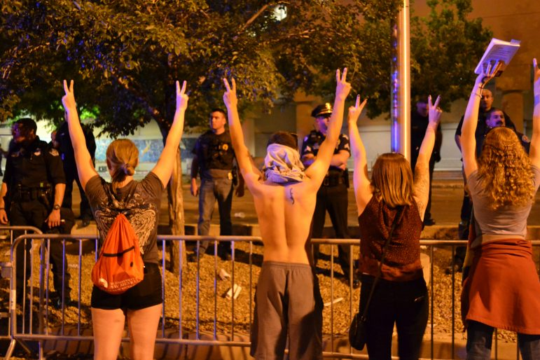 Protesters calling for peace while standing across the barrier from police.