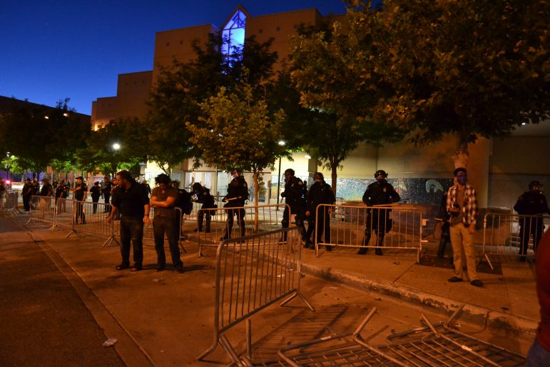 Albuquerque police move barriers forward as protesters throw rocks.