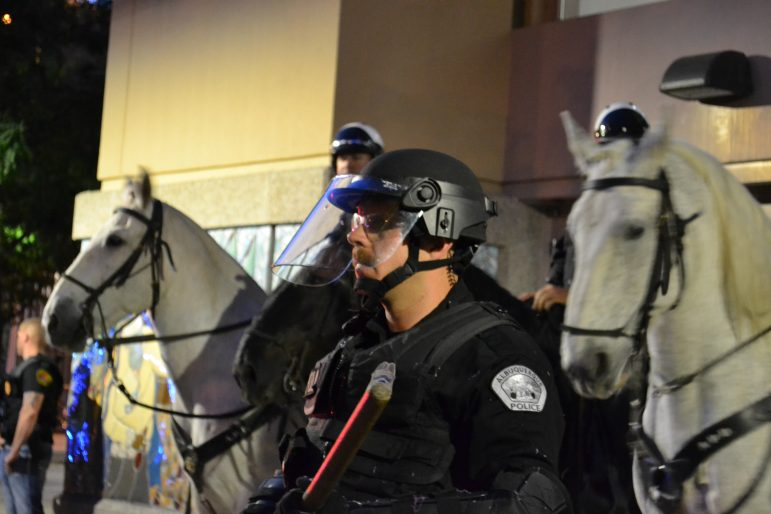 Albuquerque police stand between protesters and the Albuquerque Convention Center.