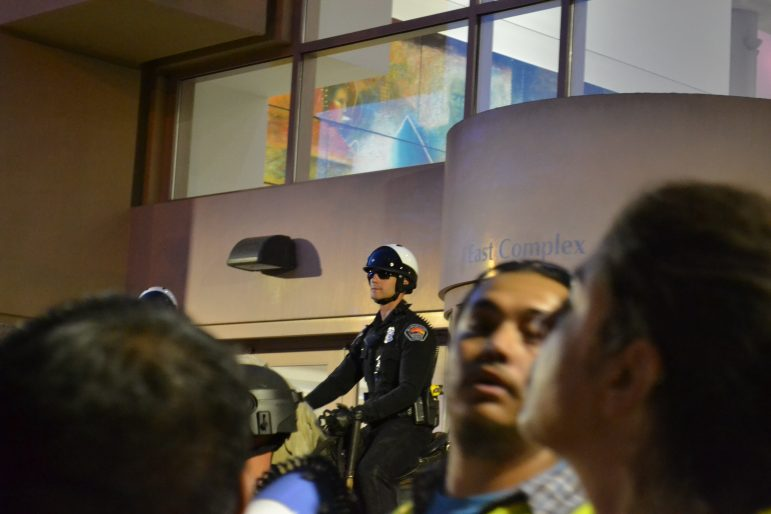 A mounted police officer stands between protesters and the Albuquerque Convention Center.