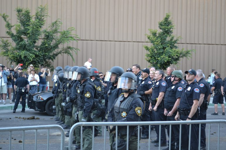 Police, including some in riot gear, stand outside the Albuquerque Convention Center.