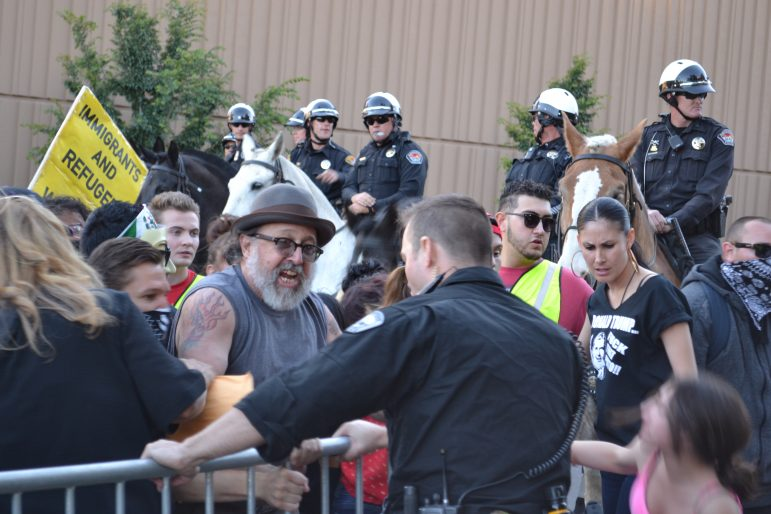 Officers try to stop protesters from breaking through barriers.