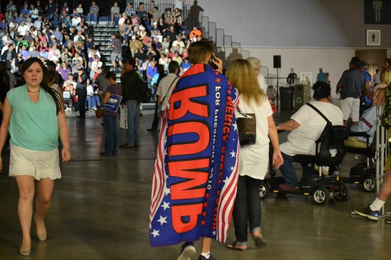a Trump supporter wearing a Trump flag as a cape.