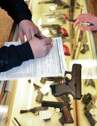 A consumer fills out a background check form to purchase a gun Wednesday at the Outdoorsman in the DeVargas Center in Santa Fe. A bill seeks to improve the background check system for gun buyers in New Mexico.