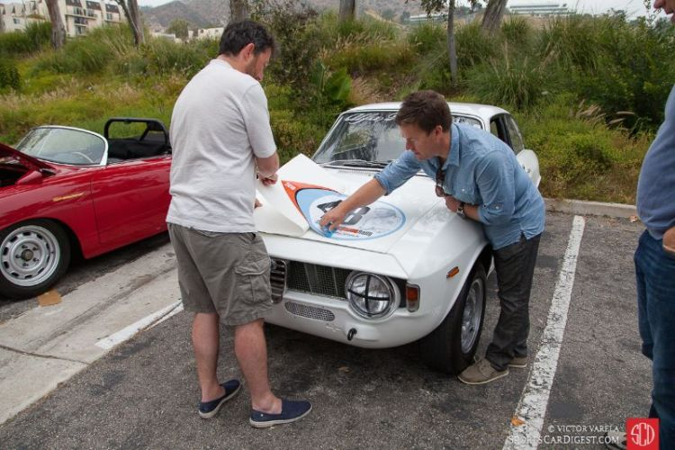 Event organizer, Gareth Ashworth places the rally decal on the 1965 Alfa Romeo GTA