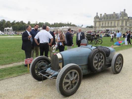 Bugatti Type 35B with the stunning Chateau de Chantilly in the background.