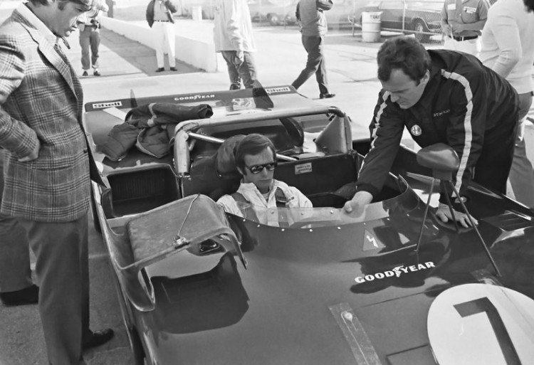 "Peter Revson being ""fitted"" for his #7 Alfa Romeo 33/TT/3.  Autodelta technical manager Gherardo Severi (far right) is explaining a few things to Revson.  (Photo by Lou Galanos)"