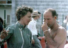 One of the great woman drivers of her time Denise McCluggage talks to British ace Stirling Moss. BARC boys photo.