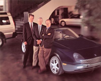 Family photo of Bruce, Kjell Qvale and Jeff alongside the Qvale Mangusta sports car at the San Francisco Dealership.