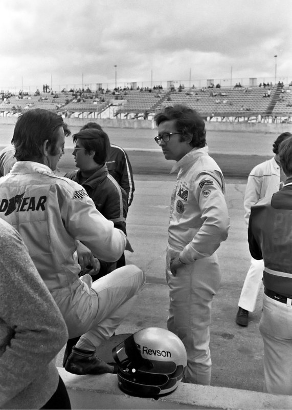 Peter Revson (back to camera) talks to fellow Alfa team driver Andrea de Adamich.  de Adamich had the distinction of being one of the few endurance and Formula One drivers who wore glasses. (Photo by Lou Galanos)