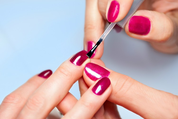 Closeup of Woman applying nail varnish to finger nails