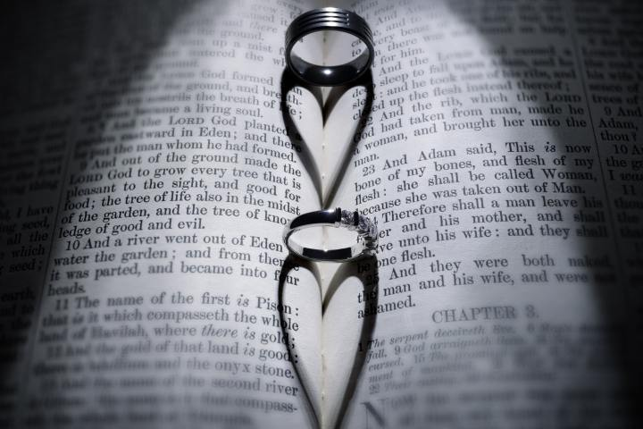 Wedding rings and heart shaped shadow over Bible