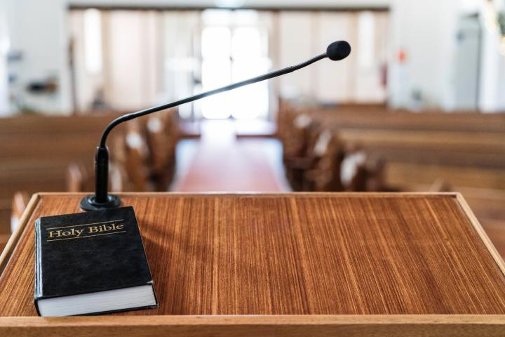 Bible on pulpit in church, with light coming in through the front door