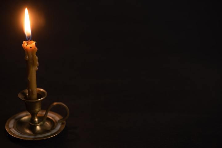 Church Candle in Candlestick Burning in Dark