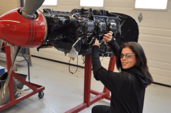 Female mechanic rebuilding an aircraft engine on a stand