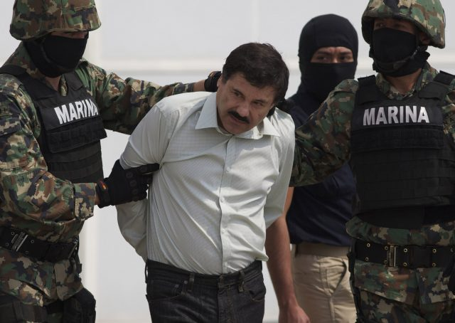 """FOR USE AS DESIRED, YEAR END PHOTOS - FILE - In this Saturday, Feb. 22, 2014 photo, Joaquin """"El Chapo"""" Guzman is escorted to a helicopter in handcuffs by Mexican navy marines at a navy hanger in Mexico City, Mexico. Guzman, the head of Mexico's Sinaloa Cartel, was captured alive overnight in the beach resort town of Mazatlan. (AP Photo/Eduardo Verdugo, File)"""