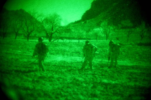 Explosive ordnance disposal technicians from one of Afghanistan's commando units sweep for improvised explosive devices during a nighttime operation.