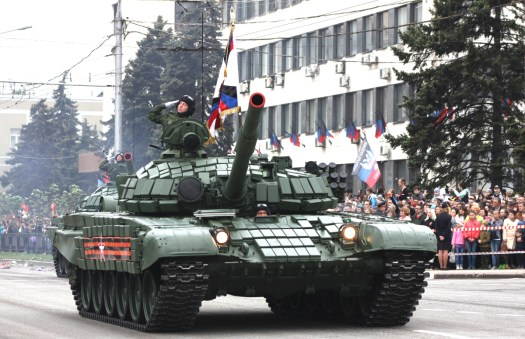 Soviet-era T-64 tanks belonging to Russian-backed separatists participate in a parade to mark the end of World War II in 2017. Note that these vehicles are wearing the exact <a href=