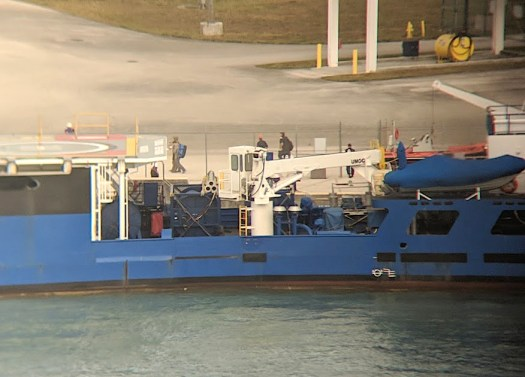 Personnel leave the Florida Explorer after the apparent conclusion of the drill. A member of the crew is visible wearing an orange hardhat. Other individuals appear to be from the uniformed force.