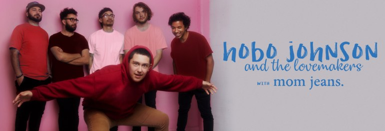Hobo Johnson in a red hoodie surrounded by 5 members of the Lovemakers dressed in pink t-shirts against a pink wall.