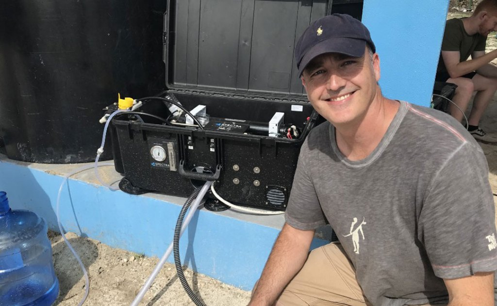 World Hope International CEO John Lyon with a state of the art machine that can transform sea water into fresh, drinkable water.