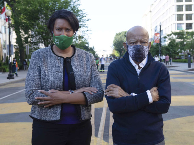 In this June 7, 2020 photo provided by the Executive Office of District of Columbia Mayor Muriel Bowser, Mayor Bowser and John Lewis look over a section of 16th Street that's been renamed Black Lives Matter Plaza in Washington. The White House is in the background. Lewis, a lion of the civil rights movement whose bloody beating by Alabama state troopers in 1965 helped galvanize opposition to racial segregation, and who went on to a long and celebrated career in Congress, died. He was 80. (Khalid Naji-Allah/Executive Office of the Mayor via AP)